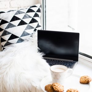 Cozy everyday breakfast with laptop, cup of coffee and cookies on ceramic tray, light white home interior decoration closeup