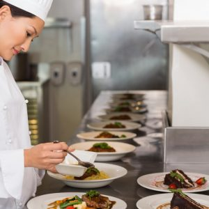 Side view of a female chef garnishing food in the kitchen